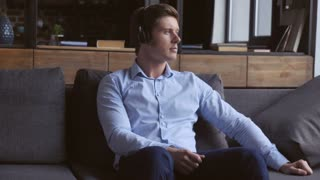 Young caucasian man resting enjoy relaxing music at home. Handsome guy sitting on the sofa studio apartment using headphones wearing elegant blue clothes