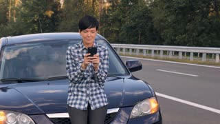 Young Caucasian woman standing nearby broken car texting message on smartphone. Attractive brunette with short haircut using mobile phone chatting or surfing internet on the roadside
