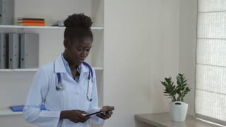 Young doctor standing with happy candid smile in hospital. Afro american woman wearing medical uniform white coat and phonendoscope holding digital tablet. Smiling professional staff in clinic