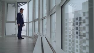young employer quenches thirst wearing in elegant suit. handsome businessman drinking water at home or in office looking on the street with urban landscape and high rise building. Successful
