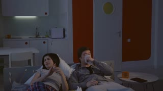 Young family lying on the bed at night at home. Attractive woman and handsome man wearing in sleepwear suffer from a cold. Caucasian couple using napkins and have fun in flat