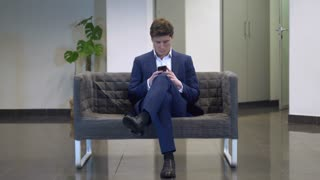 Young fashionable businessman using smartphone texting message sitting on the sofa. Caucasian young man play game on mobile phone going out leave waiting room