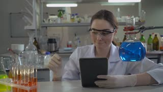 young female holding glass bulb and entering data on touch screen tablet. Attractive caucasian lab technician performs medical tests alone in office. Scientist sitting at the working place with