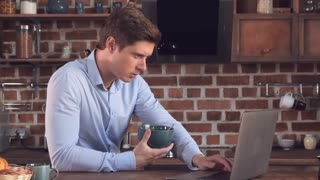 Young handsome man eating cornflakes with milk and using laptop in the kitchen. Happy smiling businessman reading news on computer and enjoy breakfast in apartment