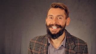young hipster man with beard posing on background in studio. handsome caucasian guy wearing casual shirt and trendy jacket. happy millennial looking at the camera and laughing