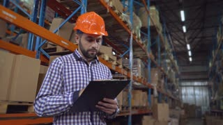 Young man checks list in documents. Handsome young employee working at warehouse. Manager wearing hard hat checking and count up goods or boxes for delivery. Man focused writing some notes