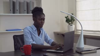 Young professional businesswoman finalising project turn off laptop and resting with happy smile. Afro american woman wearing casual shirt sitting at the working place in modern office