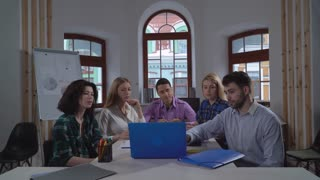 Young professional people talking looking on screen laptop with digital presentation. Staff wearing in casual dress sitting in the modern contemporary office. Workers agree with manager