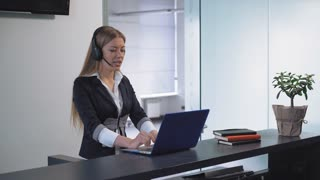Young professional woman receptionist standing at reception desk talking with client check information in computer. Smiling female with long blond hair using hands free in office. Friendly worker in