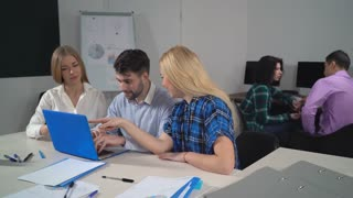 Young team have fun at work. Coworkers looking on screen laptop and laughing in office. Business people watching funny video or comical photos in social net. Handsome man chatting with friends
