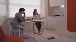 Young woman and man discussing new project or financial report at home. Couple working in startup and discuss work. On the table breakfast food and laptop in modern apartment