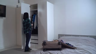 Young woman packing suitcase at home. Happy female pack up clothes in travel or business trip. Brunette choose what she want dress in vacation