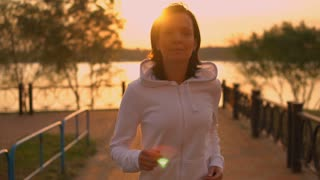 young woman running at sundown. attractive fit runner exercising alone in the evening. caucasian girl wearing hoodie enjoy healthy life. slow motion