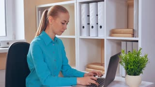 young woman sitting at workspace using laptop showing hand gesture quiet! attractive business worker in startup company wearing casual bright shirt typing on computer