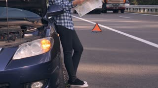 Young woman standing near broken car holding paper map on the driveway. Brunette with short hair wearing casual trendy jeans and shirt lost or checking direction way
