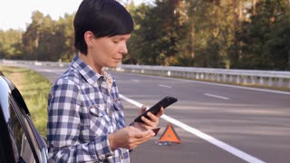 Young woman standing on the driveway near broken car holding card and mobile calling local garage or mechanic. Caucasian young female talking by smartphone on the roadside