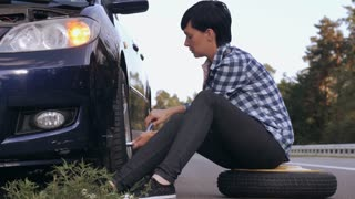 Young woman stuck on the side of the road with a flat tire. Caucasian brunette driver change a tire at the roadside