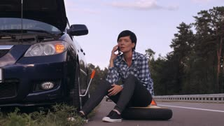 Young woman stuck on the side of the road with a flat tire. Girl sitting on the spare tire at the roadside calling for help or has phone conversation with friend