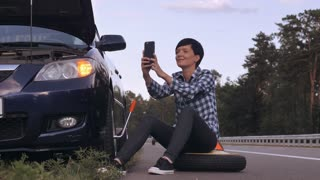 Young woman stuck on the side of the road with a flat tire. Girl sitting on the spare tire at the roadside taking selfie photo posing smiling using smartphone sharing photography in social media