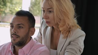 Young woman with blond hair and mixed race man close up portrait looking on display computer talking about business project. Attractive friendly people discussing with happy smiling emotions