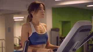 Weight training in gym. Woman with long hair trains on cardio machine. Girl warming up on cross trainer. Attractive female doing exercises dressed in blue top