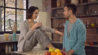 Wife and husband talking and drinking water in the kitchen. Happy family enjoy and have fun in the morning in flat. Attractive brunette holding glass. Handsome man telling some funny story