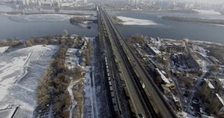 Winter, on the slopes of snow on the bridge train rides across the river, near the road going car