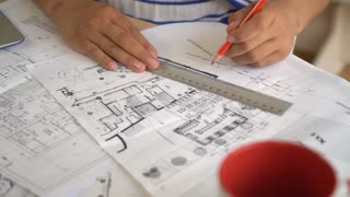 Woman architect correct design and draftsmanship on architectural sketch. On the wooden desk plan new building or house or flat. She using red pencil and line. Mixed race women's hands drawing on