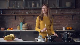 Woman cooking dinner has video call conversation in kitchen. Smiling happy female talking with friend using application on computer. Caucasian model gossip and tastes sauce. On the cooking table