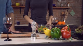 Woman cooking in the kitchen. Female hand holding handheld pepper mills. Lady peppering salad in a bowl. Man taking wineglass with red wine. On the cook table different vegetables and fruits. People
