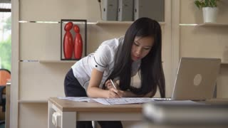 Woman designer standing near working place drawing on architectural plan