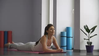 Woman doing   exercises for flexibility in gym on the floor