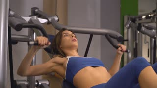 Woman doing exercises on biceps training machine in gym. Caucasian bodybuilder trains alone. Young beautiful woman working out lifting weights. Girls wearing in blue sport top