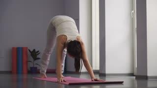 Woman doing yoga exercises downward facing dog pose.