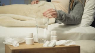 Woman drinking drugs lying in bed.