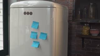 Woman going to the fridge at home. Adult lady taking off two blue sticky notes. Caucasian adult model in the kitchen