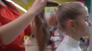 Woman hairdresser makes ponytail little caucasian blonde girl. Female barber combing hair child using comb