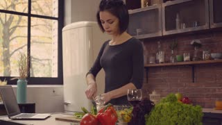 Woman learning how to cook dinner. Young girl trying to cut vegetables and laughing. Caucasian brunette have fun on the kitchen. Attractive model wearing in casual dress standing near wooden table