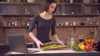 Woman make salad on kitchen at home. Happy wife or girlfriend waiting family or friends for dinner. Brunette standing in loft room near cook table wearing in elegant dress. On the deck computer with