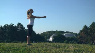 woman raising her hands. Beautiful athlete warming - up body before workout. Caucasian girl with long blond hair stretch muscles in the park. blonde doing exercises for arms stand on the meadow in the