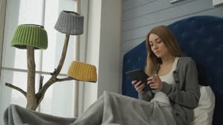 Woman sitting on a bed with a tablet.