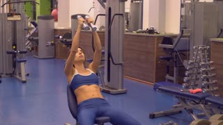 Woman with long blond hair doing exercises with light weights wearing in blue top and leggings. Slim lady training arm sitting on sport machine. Everyday workout for biceps