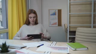 Woman with tablet sitting in the office