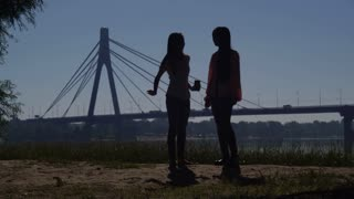 women silhouettes dancing in the city. Girls standing on the beach near the river. Happy girls celebrating success. On the background modern bridge with riding cars. City view with beautiful landscape