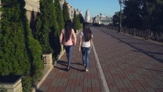 Women walking in the city along street cafe. Two asian female with long black hair going on the pavement. Friends wearing in stylish jeans and casual top. Rear back view