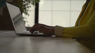 Women's hands computing on the laptop at working place. Mixed race model wearing in casual stylish yellow jacket