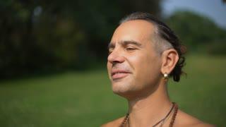 Yogi man with eyes closed smiling and enjoying the sun