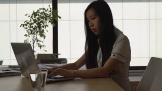 Young asian woman sitting in the office working with computer. Lady wearing in elegant formal shirt in room with big panoramic windows
