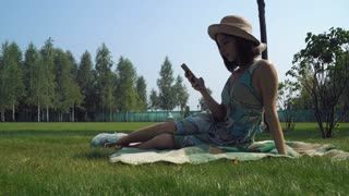 Young brunette girl in a hat sitting on blankets in the summer park and gaining a message on the phone. Smiles
