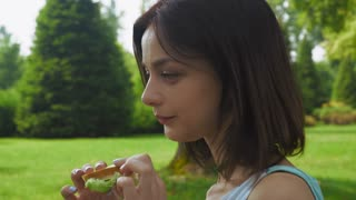 Young brunette girl sitting sideways in the park on a sunny day and eat a sandwich with salad. Close up
